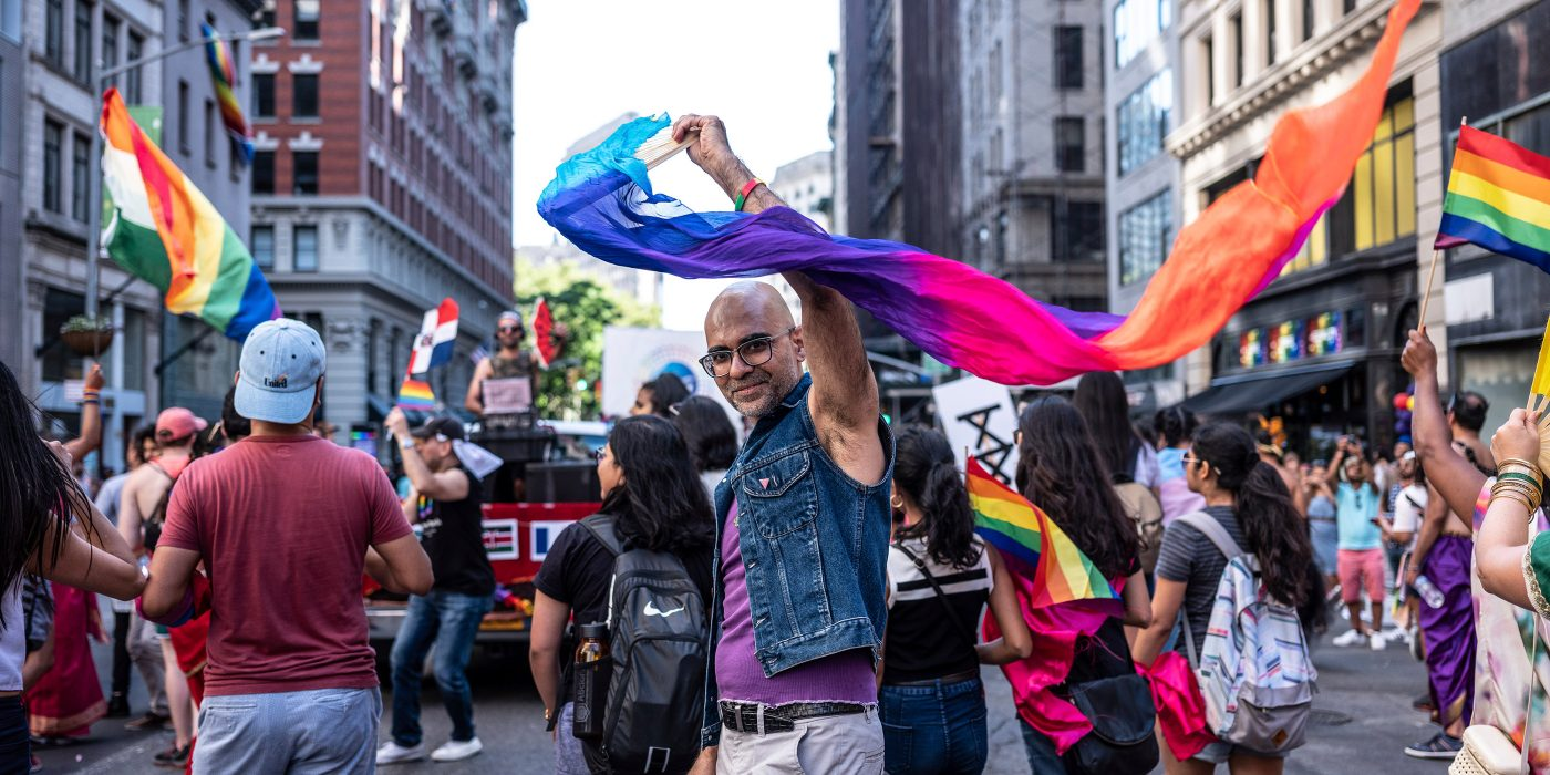 A man holds aloft a rainbow scarf for Pride day
