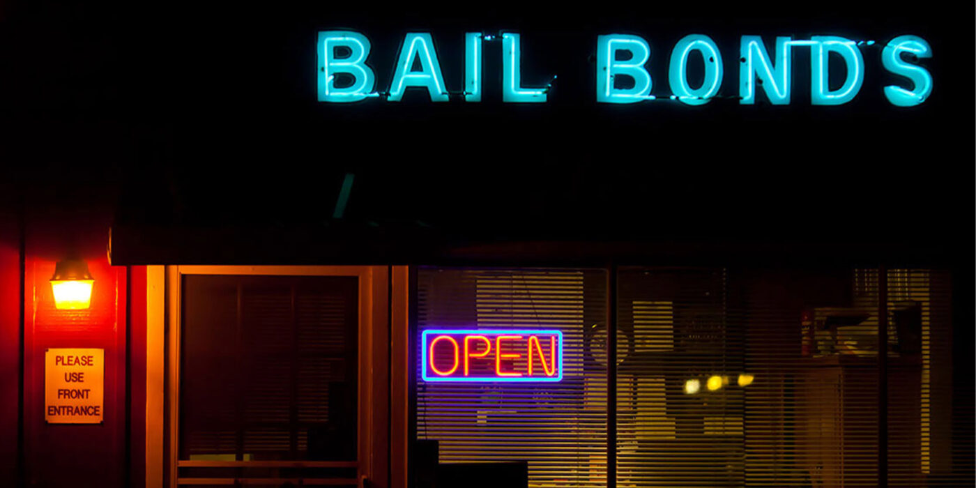 "The front of a location with a bright blue neon sign that reads ""bail bonds"" taken in the middle of the night."