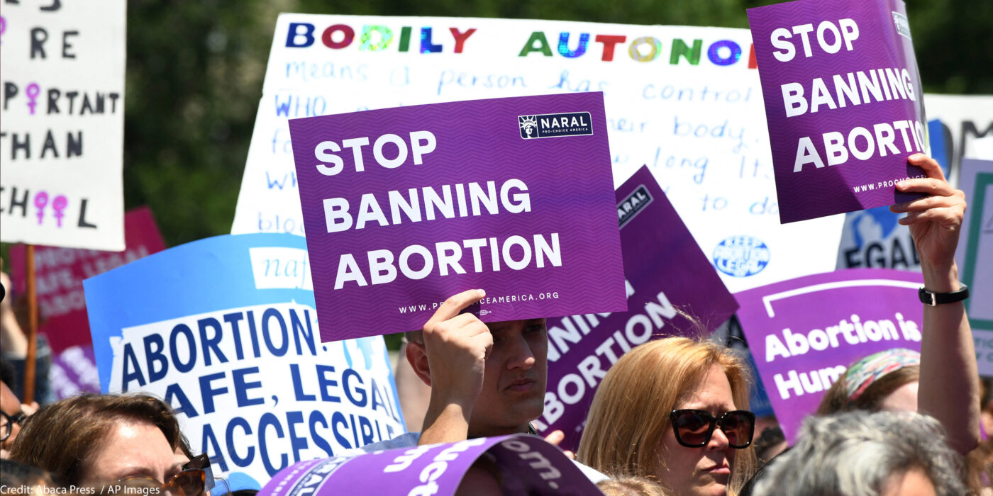 """Pro-abortion activists hold placards that read """"Stop Banning Abortion"""" during a rally at the Supreme Court."""