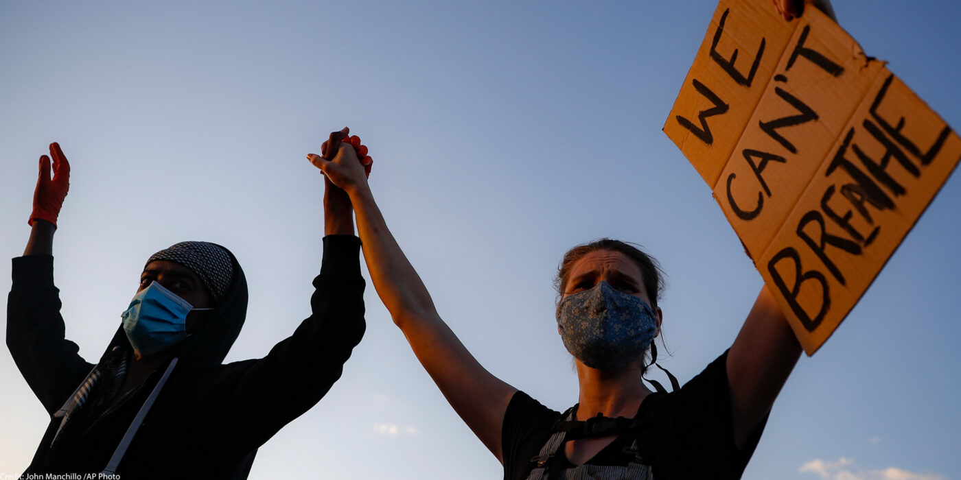 "Protestors demonstrate in Minneapolis while holding a ""WE CAN'T BREATHE"" sign and wearing protective masks"