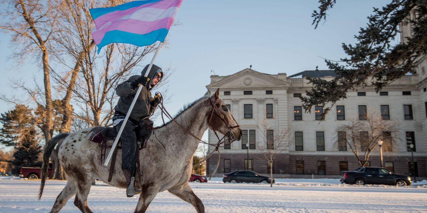A man horseback riding in the middle of the day through the snow in South Dakota holding the transgender pride flag after an anti-trans bill was defeated in the state.