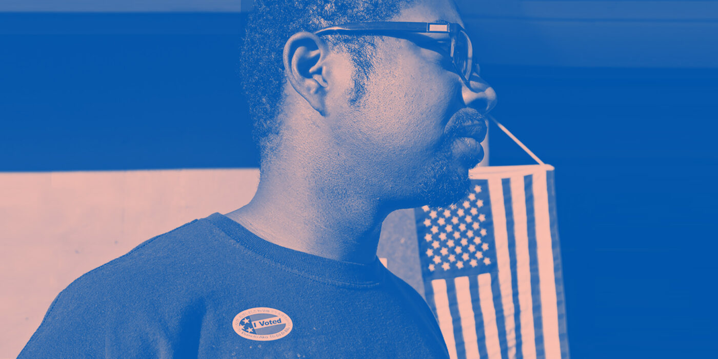 """A man wears an """"I Voted"""" stick with the American flag hanging in the background. Image tinted blue and pink."""