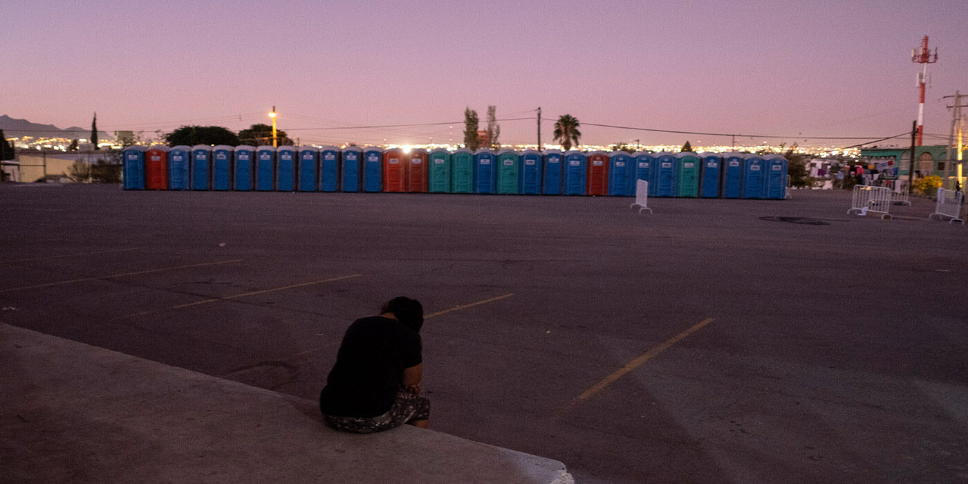 A woman sits outside in an empty lot in Ciudad Juarez, Mexico at sunset, with her head hanging down, and a line of outhouses across the lot.