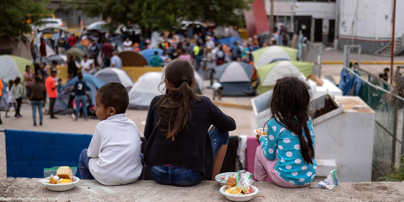 Three children sit down while eating food, backs turned to the camera. In front of them stand men, women, and children in a lot full of tents where they stay. Taken in Matamoros, Mexico.