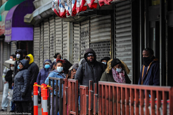 Customers in masks line up outside a grocery store in Brooklyn, NY, waiting to enter after other shoppers have left, because of social distancing efforts during the coronavirus outbreak.