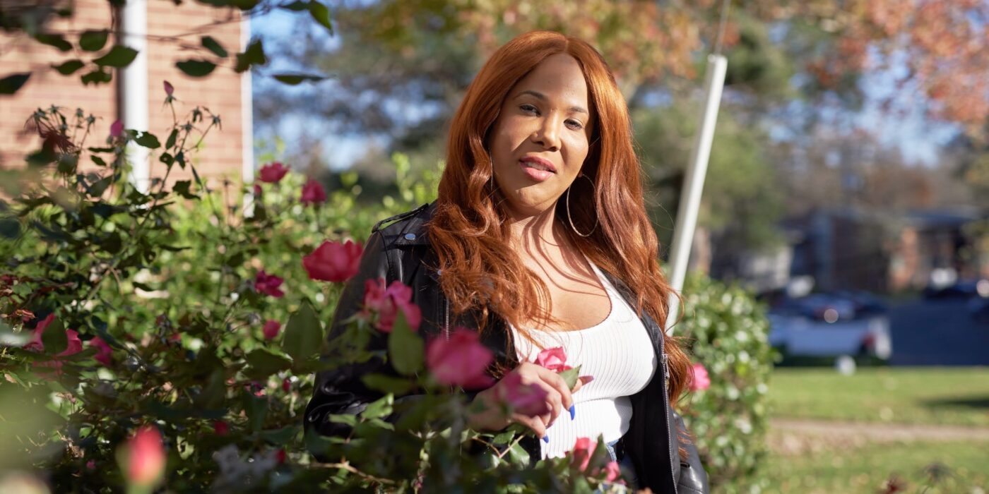 Black trans woman wearing a leather jacket standing in a garden with flowers