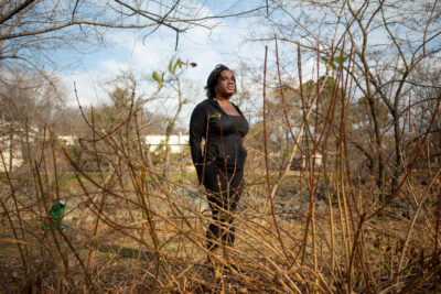 Erica Aries, Black trans woman standing in wooded area.