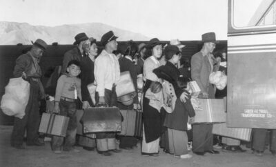 Japanese-Americans transferring from train to bus at Lone Pine, California, bound for war relocation authority center at Manzanar, April, 1942.