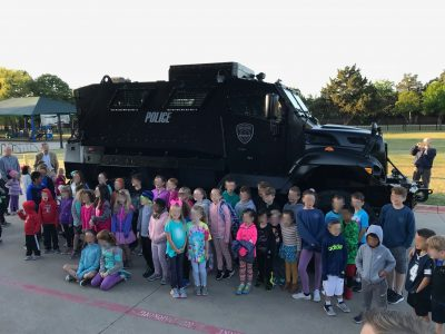 Children pose with a mine-resistant ambush protected vehicle in Southlake, Texas.